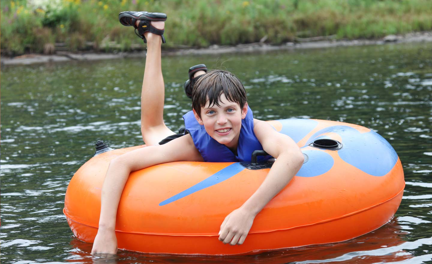 young boy smiling in tube on river Indian Head Canoeing Rafting Kayaking Tubing Delaware River