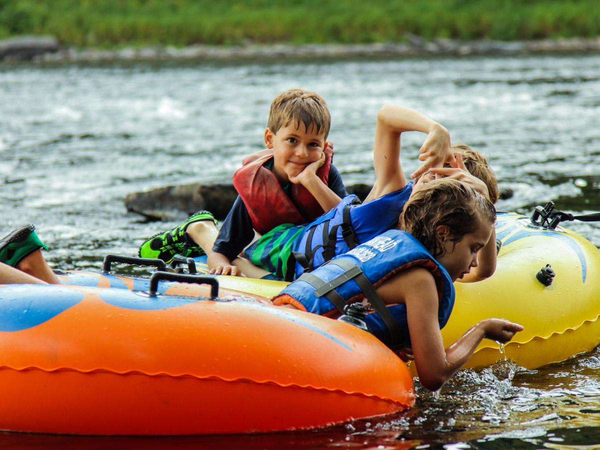 three kids taking a break in their tubes heading to Matamoras Indian Head Canoeing Rafting Kayaking Tubing Delaware River