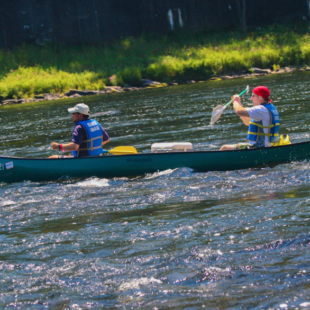 two males in long canoe on river Indian Head Canoeing Rafting Kayaking Tubing Delaware River