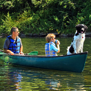dad son and dog in in green canoe Indian Head Canoeing Rafting Kayaking Tubing Delaware River