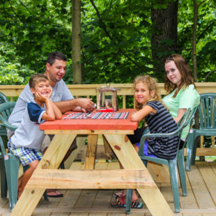 family playing Uno on bench on deck of cabin Indian Head Canoeing Rafting Kayaking Tubing Delaware River