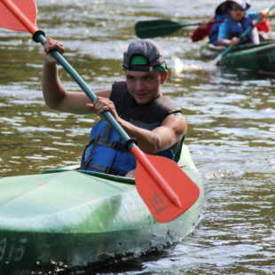teen trying to come in first in kayak in Dingmans Ferry Indian Head Canoeing Rafting Kayaking Tubing Delaware River