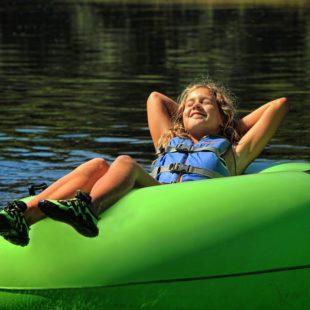 young girl soaking up sun in tube Indian Head Canoeing Rafting Kayaking Tubing Delaware River
