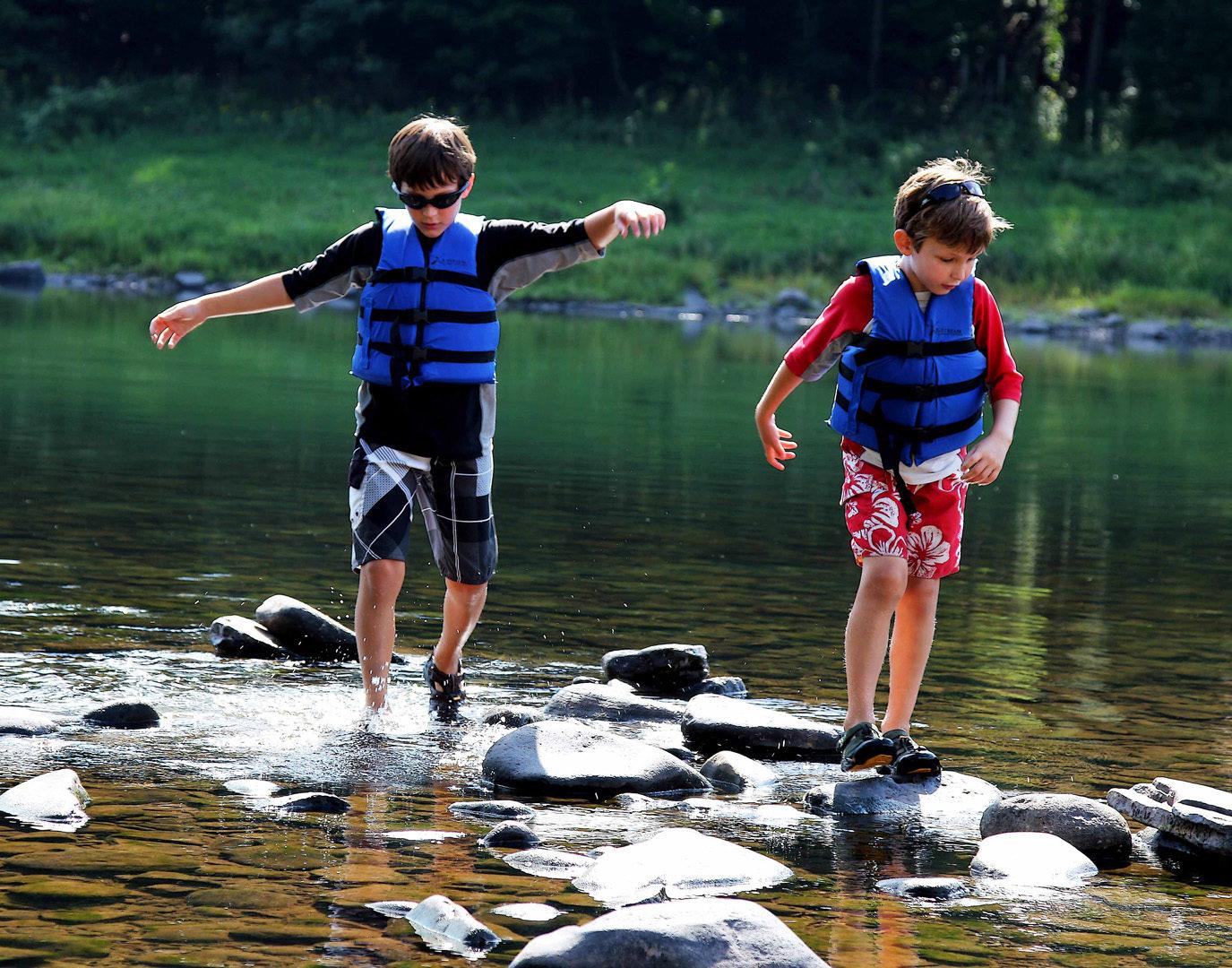two boys navigating the river rocks Indian Head Canoeing Rafting Kayaking Tubing Delaware River